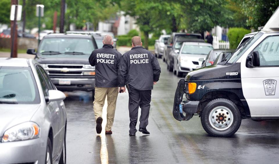 Everett police officers walked outside a house where FBI agents were investigating.